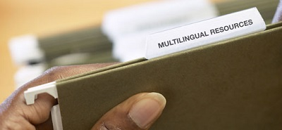 Hand on file titled 'Multilingual Resources'