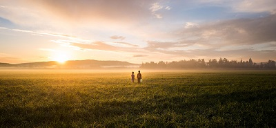 Two children in a field looking towards a brilliant sunrise in the distance