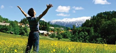 Young man standing in field of yellow flowers arms outstretched, European town in the background