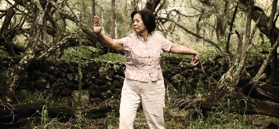Older woman practising tai chi in forest