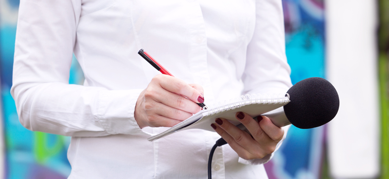 Journalist with notebook and microphone