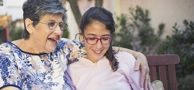 Older woman and teenage granddaughter sitting on bench outdoors looking at IPAD and smiling
