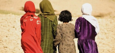Four Afghan girls dressed in bright clothing looking out at desert landscape